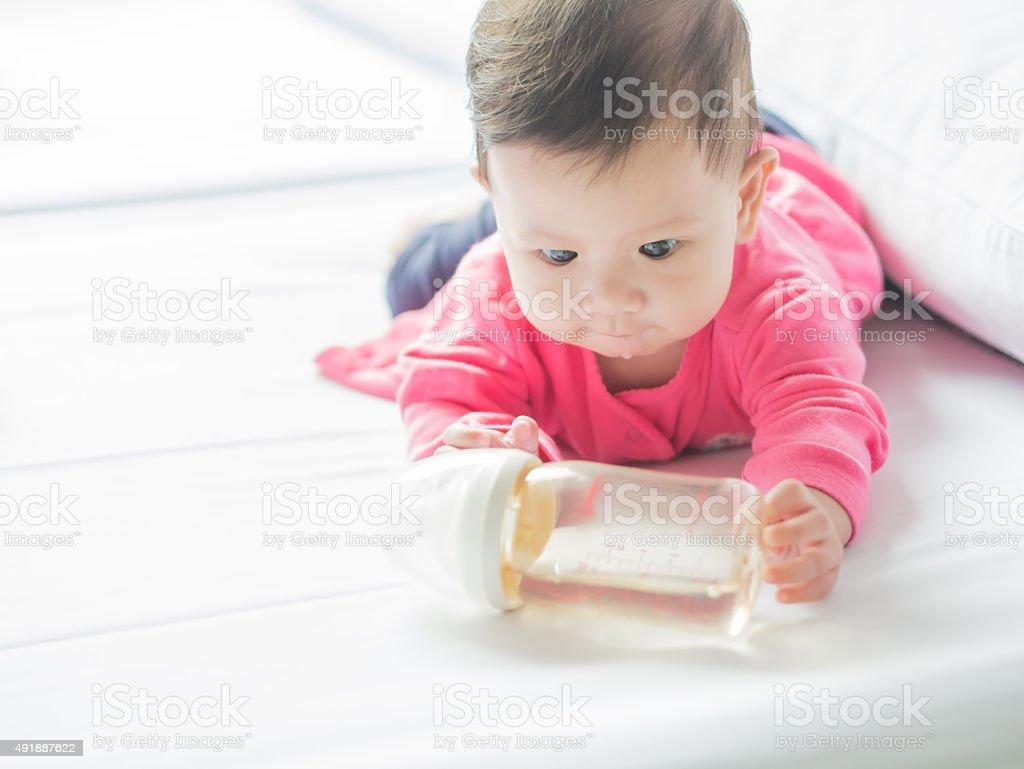 Asian baby holding milk bottle. royalty-free stock photo