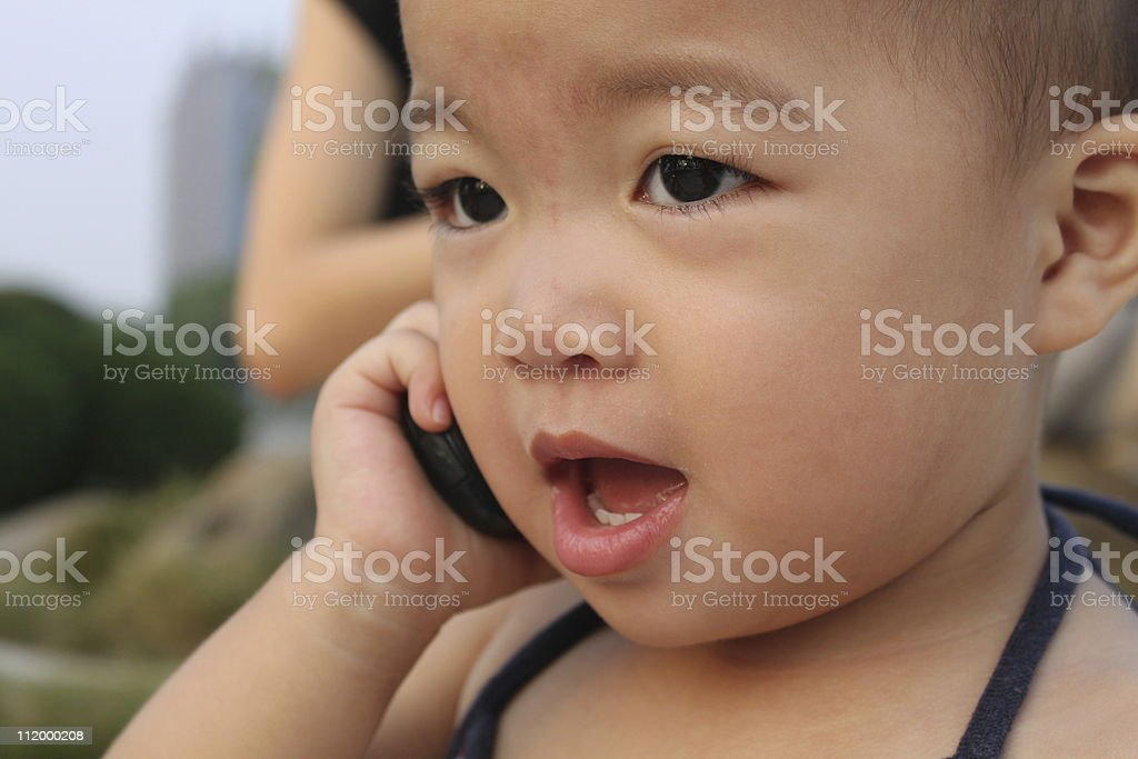 Asian baby in swim suit,murmuring to a cellphone stock photo
