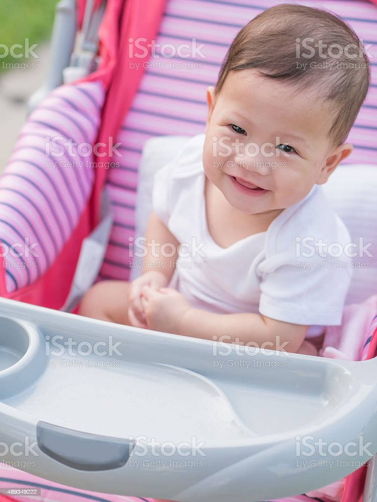 Asian baby smiling while sitting in stroller. royalty-free stock photo