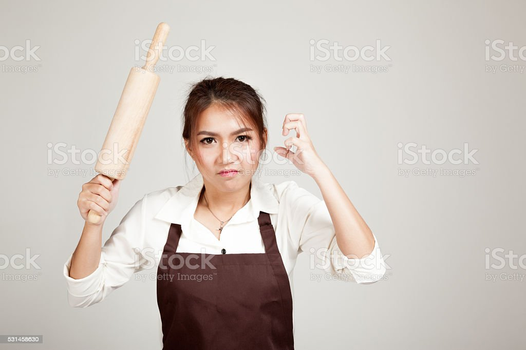 Asian Baker woman  in apron  with wooden rolling pin stock photo