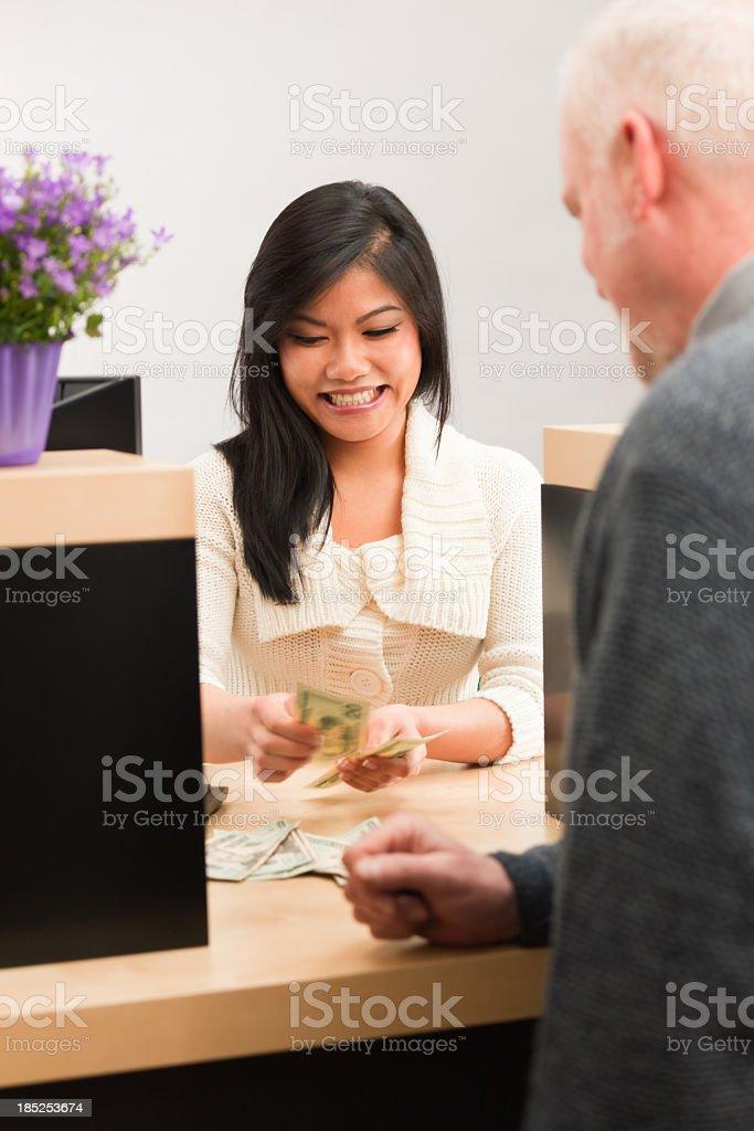 Asian Bank Teller Handing Cash, Providing Customer Service at Counter royalty-free stock photo