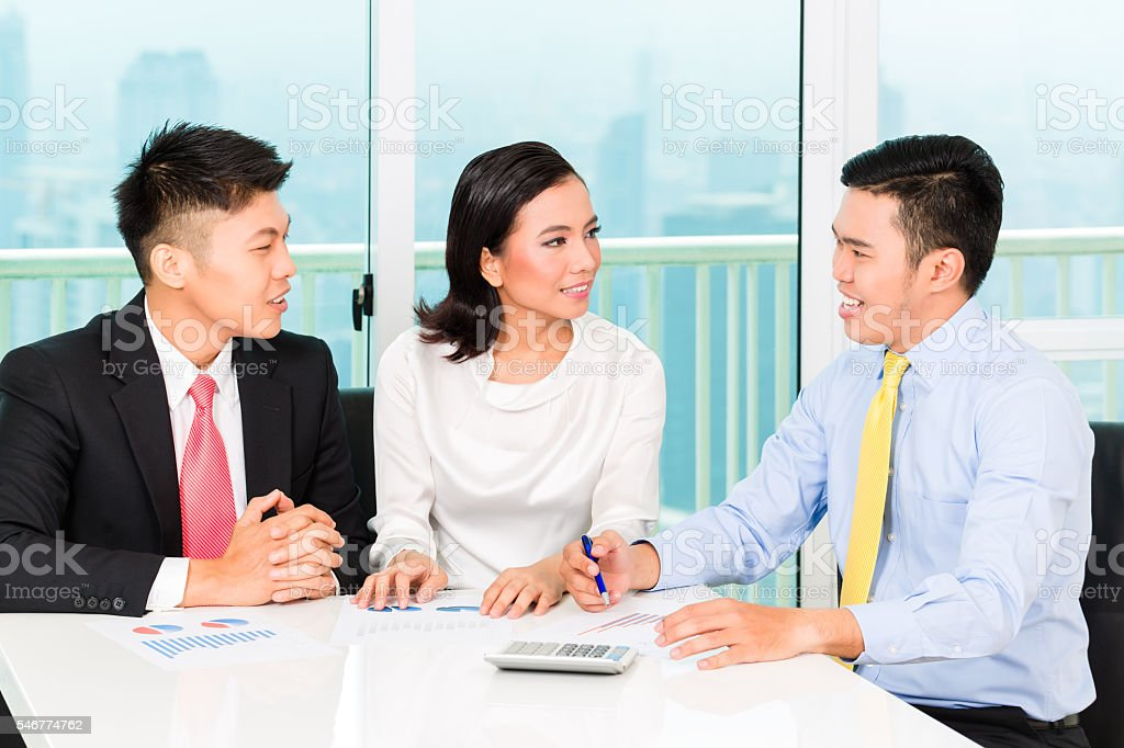 Asian banker selling insurance to couple stock photo
