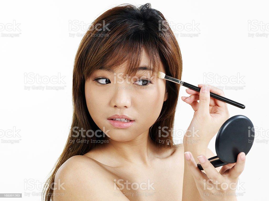 Asian beauty woman applying make-up using powder compact royalty-free stock photo
