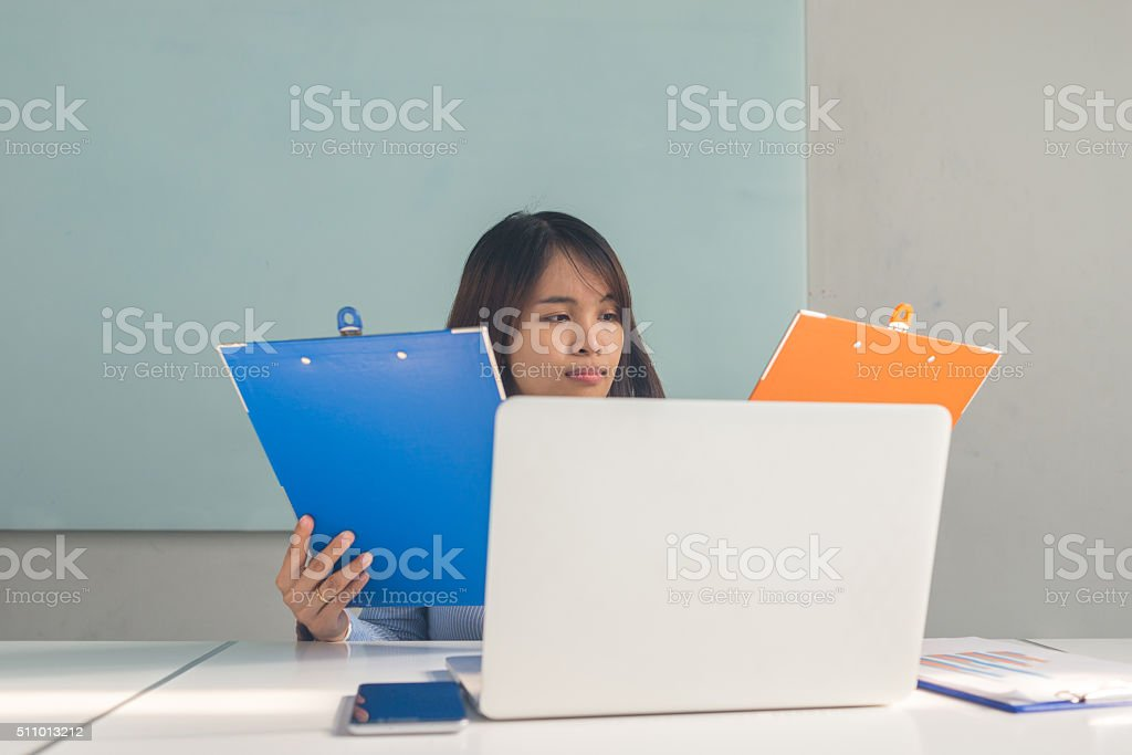 Asian boss checking the sales reports in business room stock photo