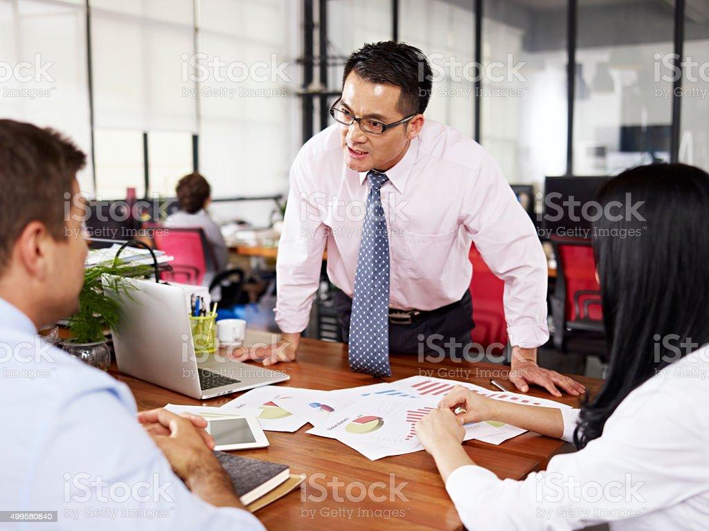 asian boss yelling at subordinates stock photo
