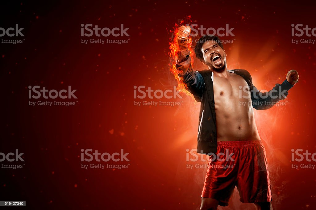 Asian boxer punching with flame around his arm stock photo