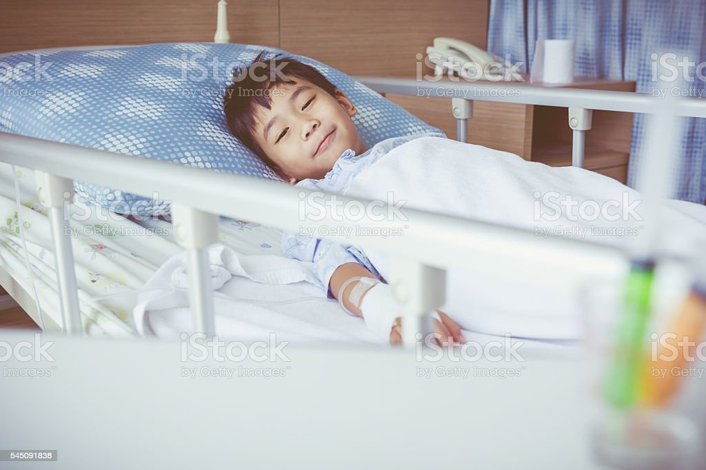 Asian boy admitted at hospital with saline intravenous (IV). stock photo