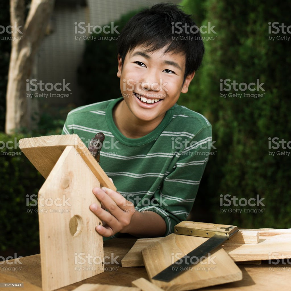 Asian Boy Building Wood Birdhouse stock photo