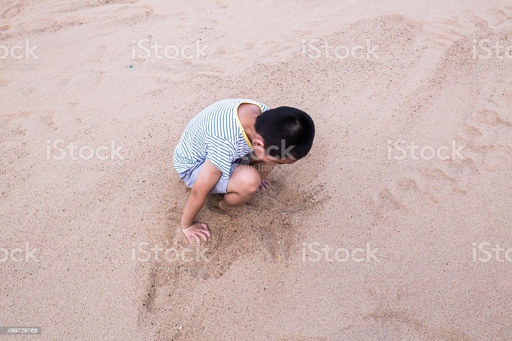 asian boy bury himself in the sand field stock photo