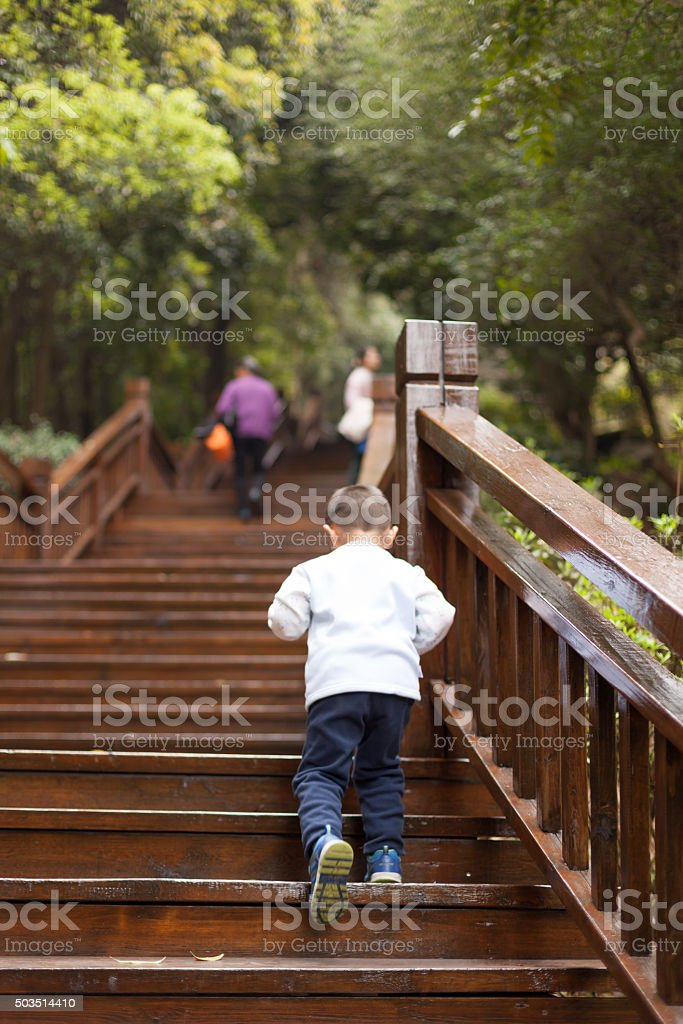 Asian Boy climb wooden stairs stock photo