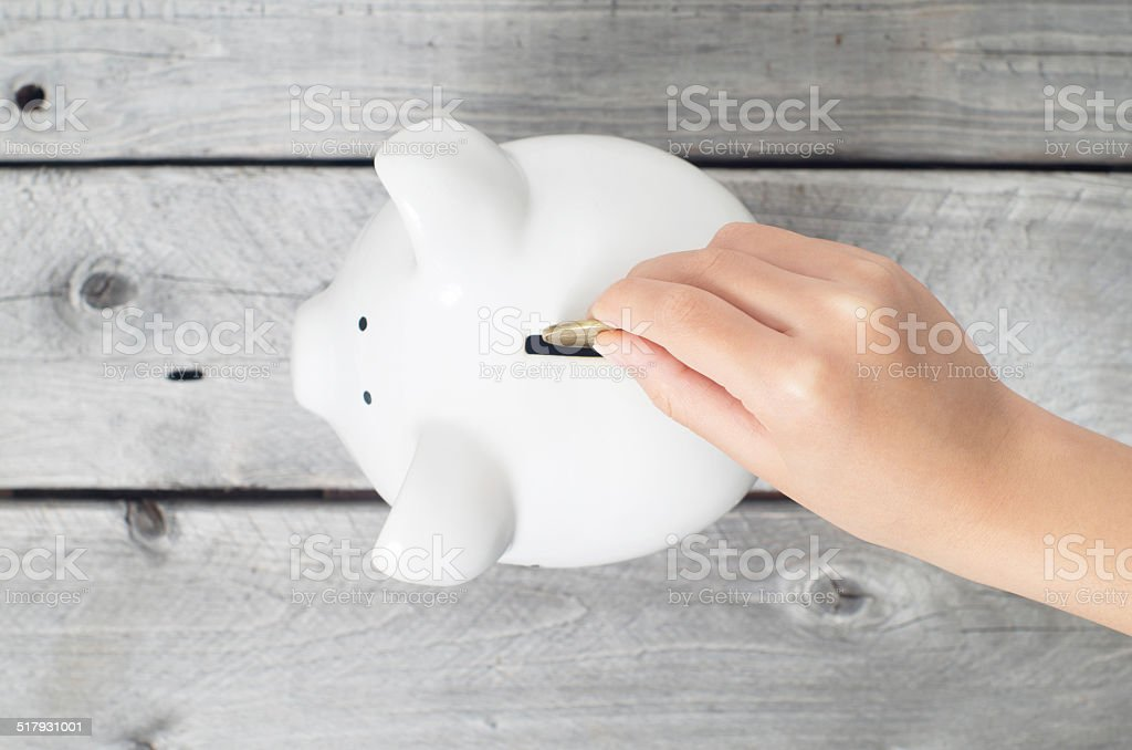 Asian boy hand dropping a coin into white piggy bank stock photo