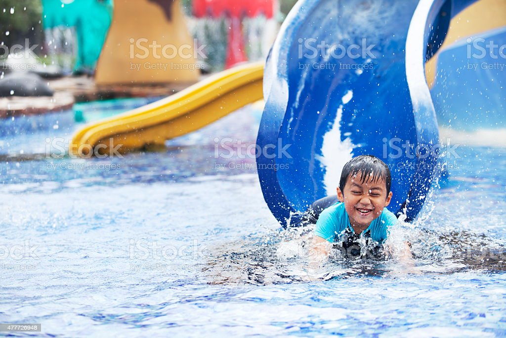 Asian boy having fun at swimming pool stock photo