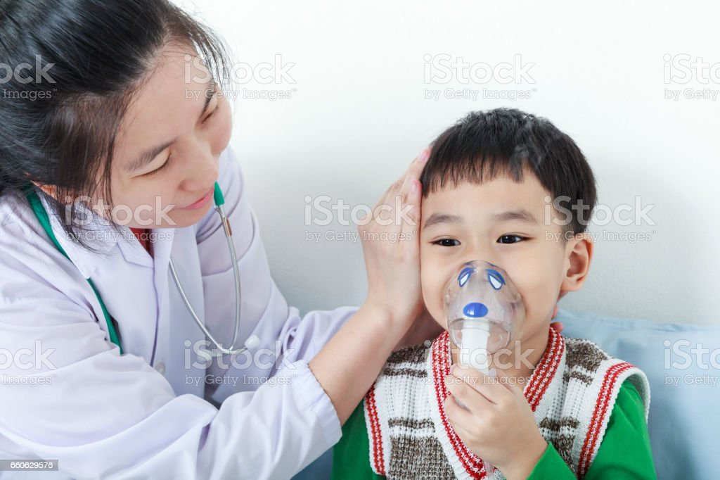 Asian boy having respiratory illness helped by doctor with inhaler. stock photo
