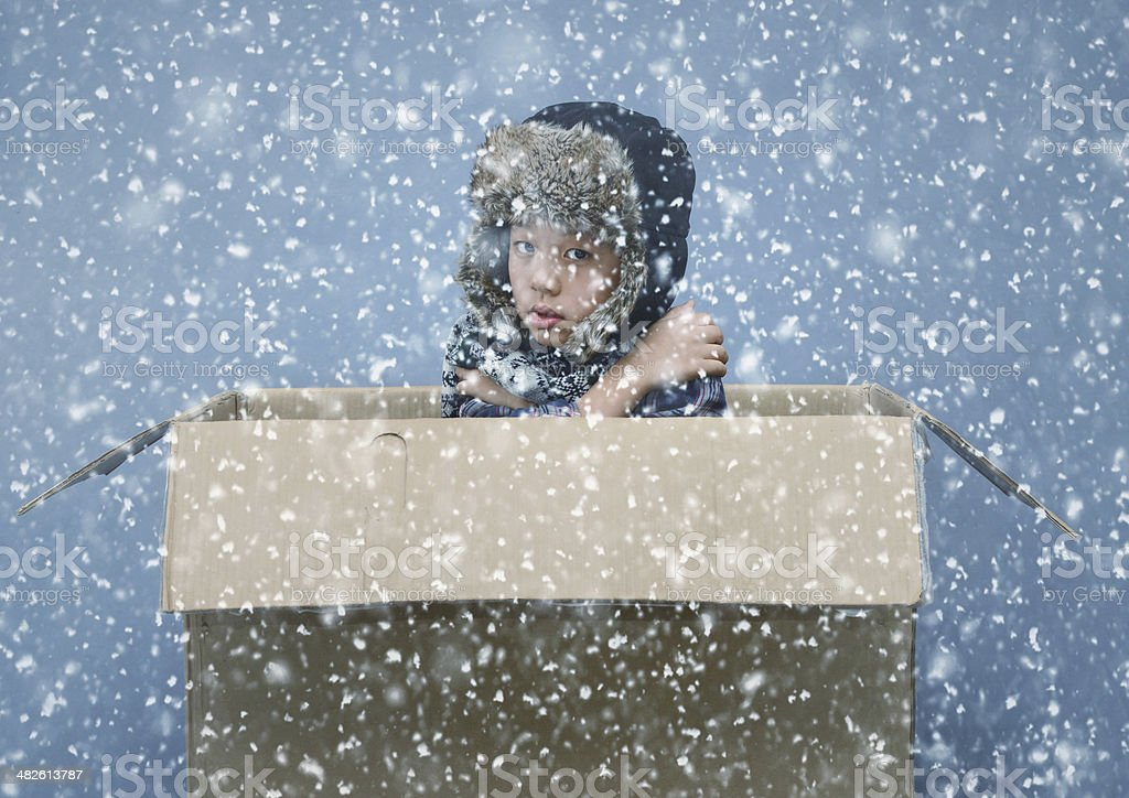 Asian boy in cardboard box during winter snowfall stock photo