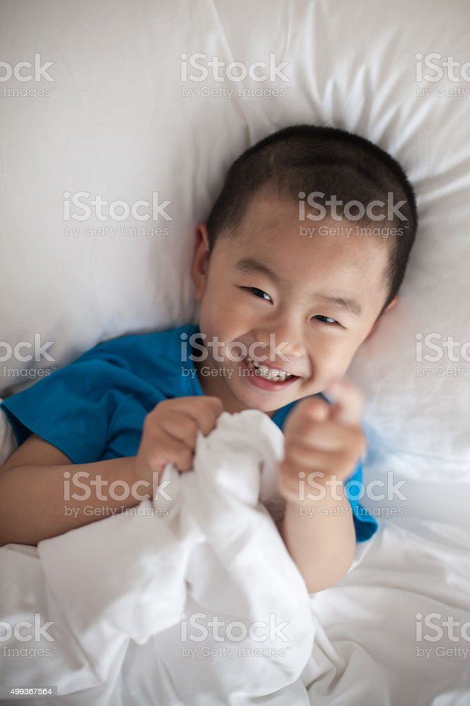 Asian Boy  in White quilt stock photo