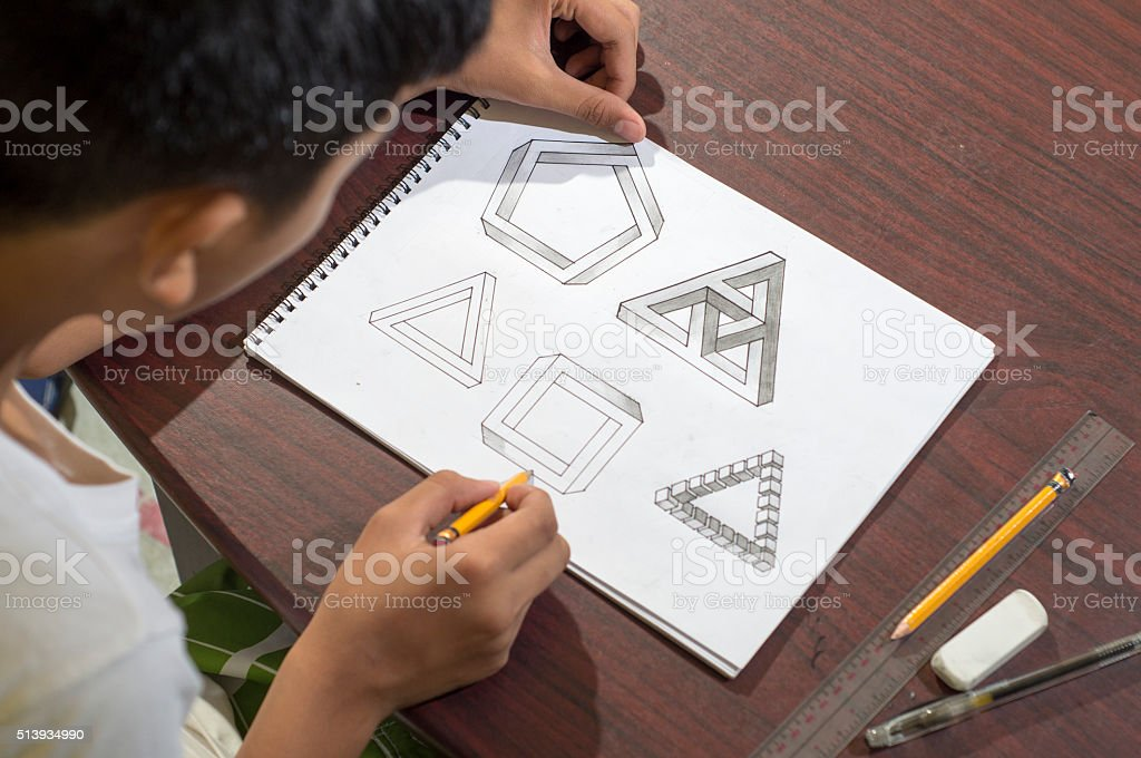 Asian boy learning and practicing to draw 3D shapes stock photo