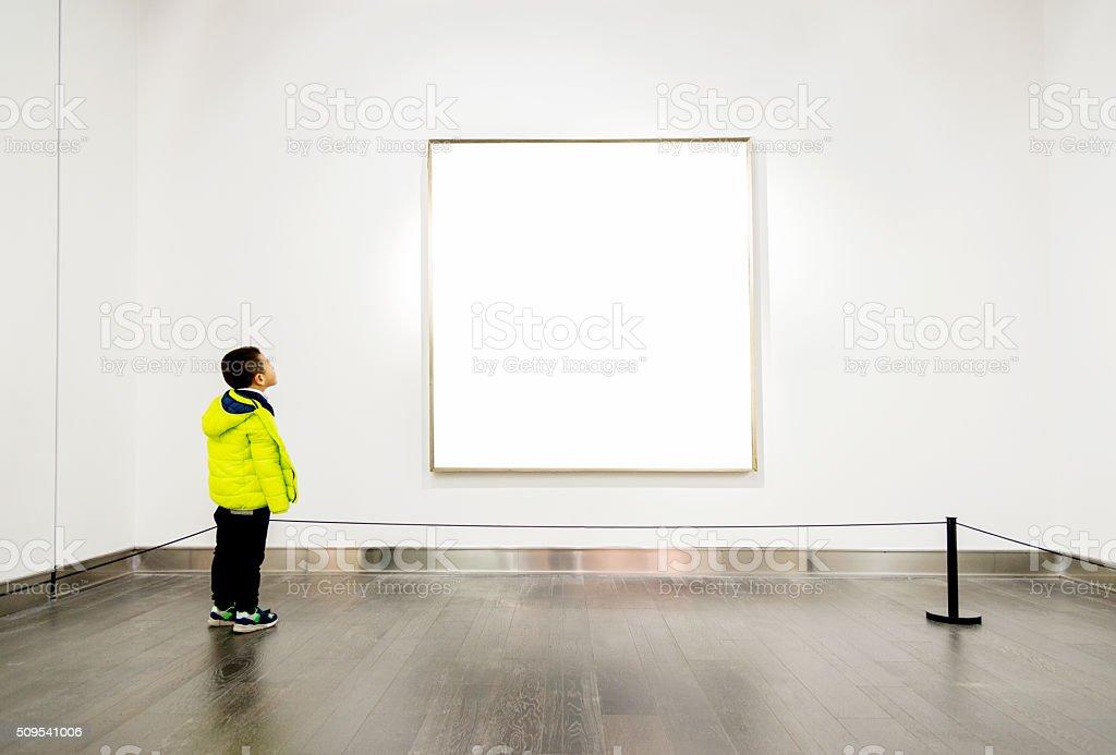 Asian boy looking at artwork stock photo