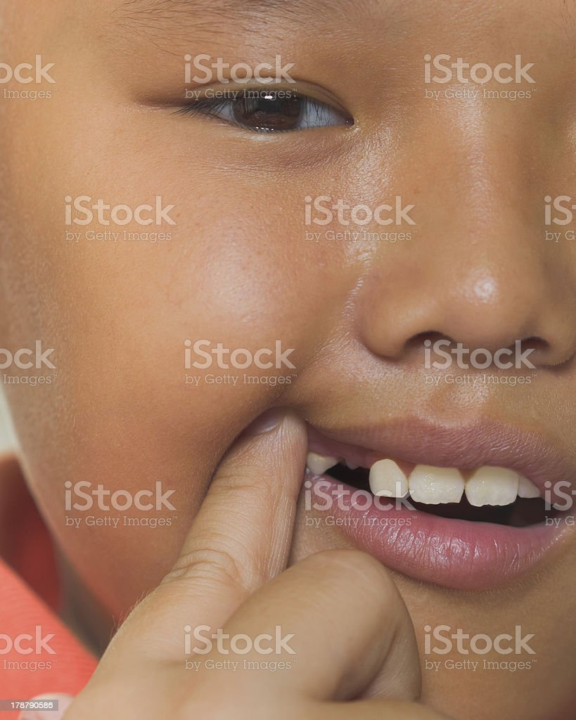 Asian boy losing his milk tooth stock photo