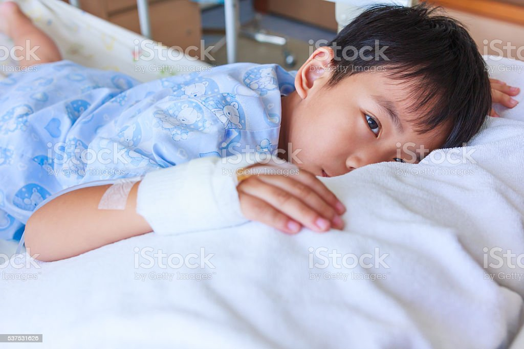 Asian boy lying on sickbed, saline intravenous (IV) on hand. stock photo