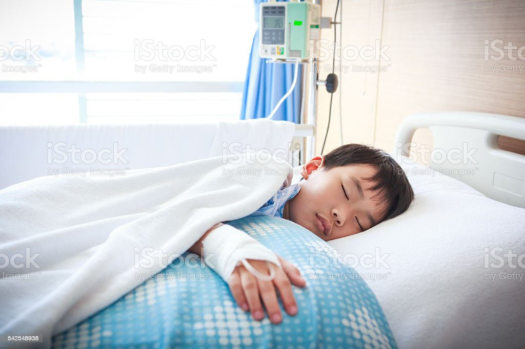 Asian boy lying on sickbed with saline intravenous (IV). Health stock photo