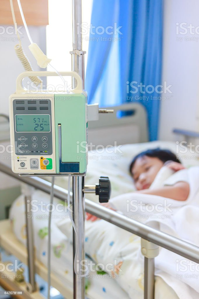 Asian boy lying with infusion pump intravenous IV drip. stock photo