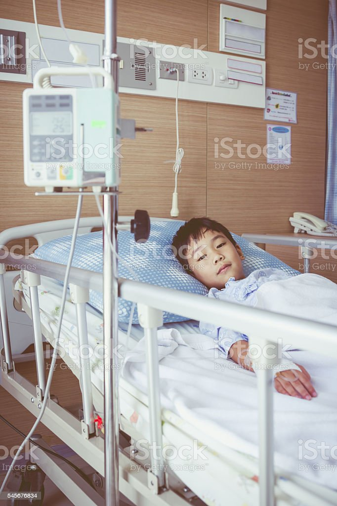 Asian boy lying with infusion pump intravenous IV drip stock photo