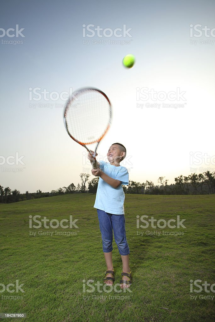 Asian boy playing tennis on the lawn stock photo