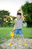Asian boy playing with toys in garden