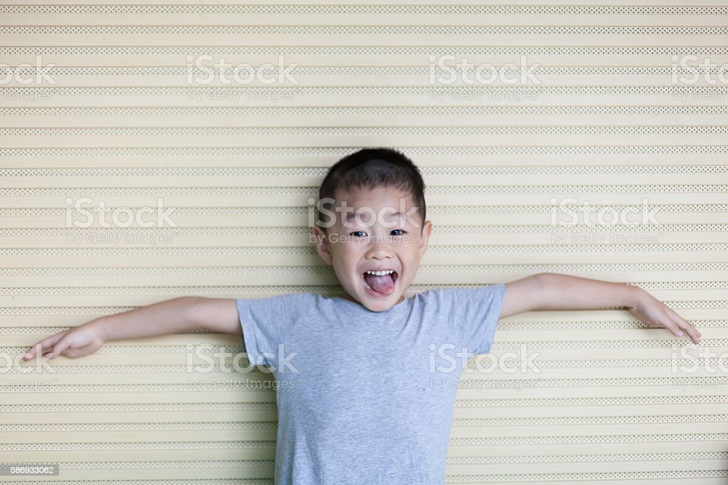 Asian boy spread arms white leaning wall stock photo