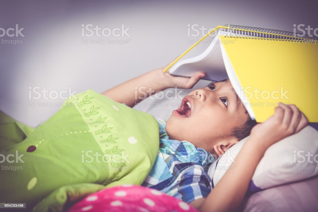 Asian boy surprised, child covering head with book. Vintage tone. stock photo