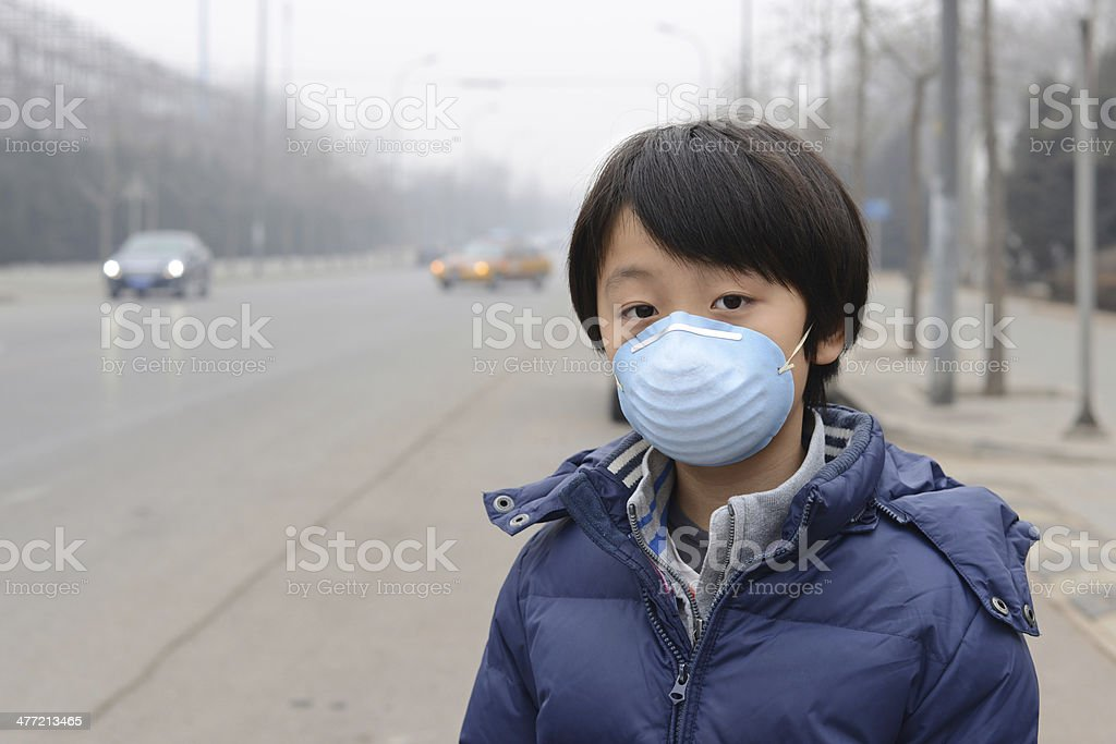 Asian boy wearing mouth mask against air pollution (Beijing) royalty-free stock photo