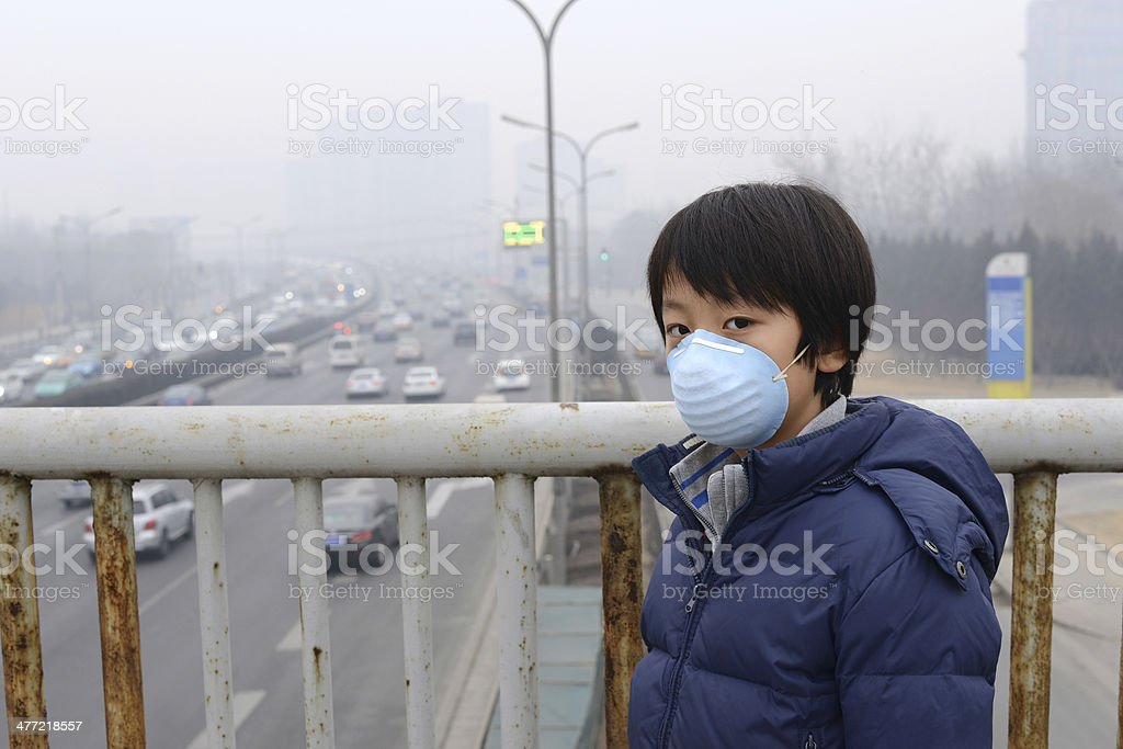 Asian boy wearing mouth mask against air pollution (Beijing) stock photo