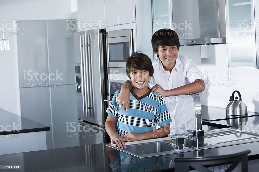 Asian boys standing in kitchen royalty-free stock photo