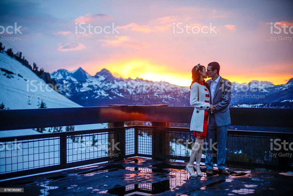Asian Bride and Caucasian Groom on Wedding Day in Mountains stock photo