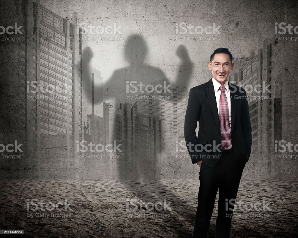Asian business man casting a shadow of strength stock photo