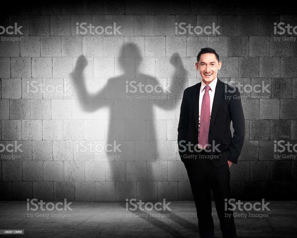 Asian business man casting a strong man shadow stock photo
