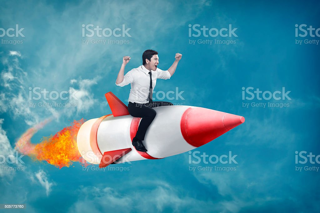 Asian business man flying ride rocket stock photo