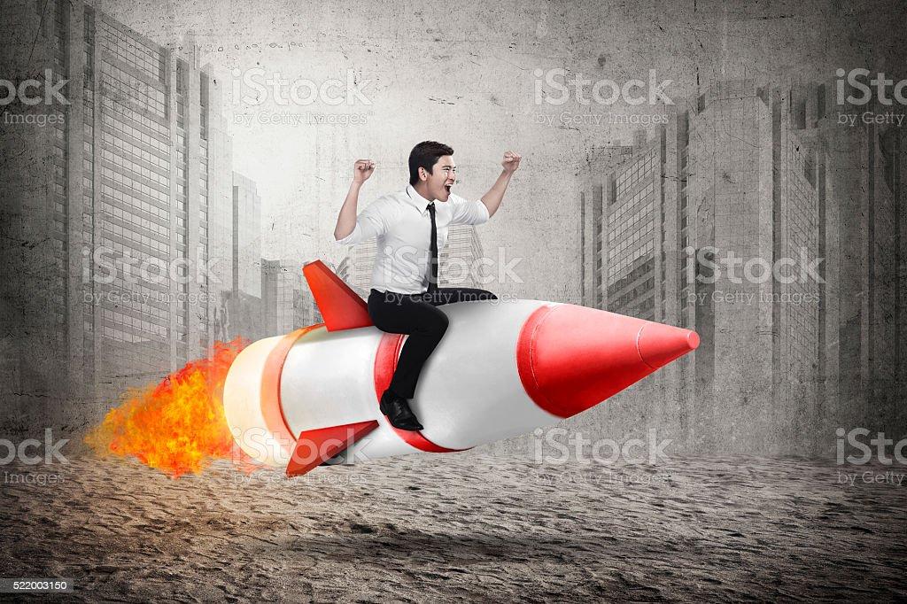 Asian business man riding rocket stock photo