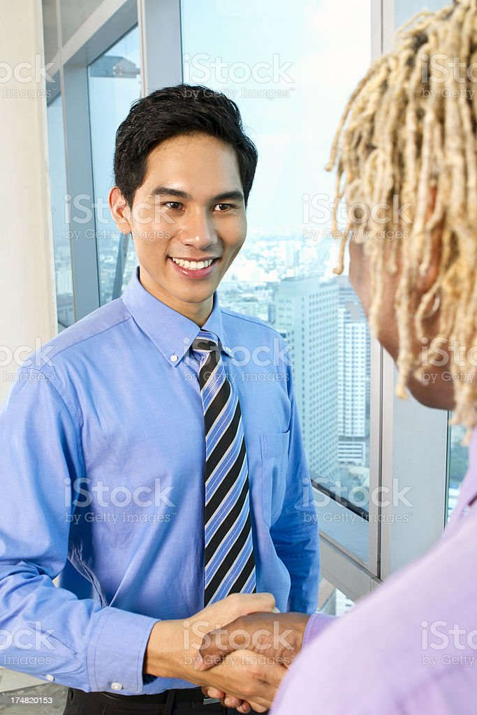 Asian business man shaking hand with partner royalty-free stock photo