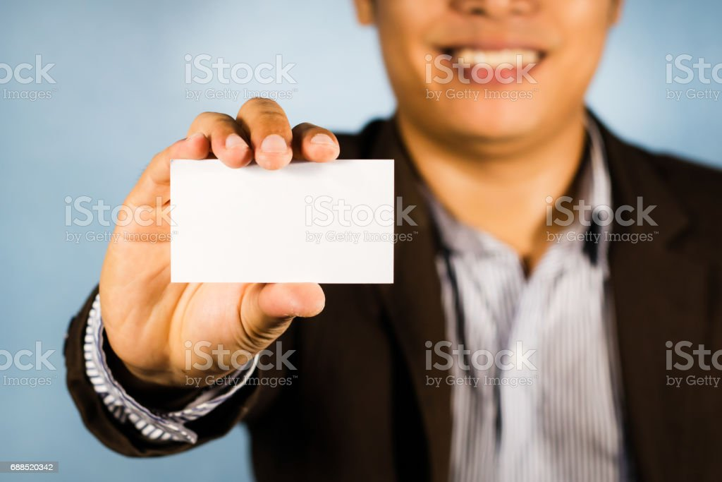 Asian business man show white card on hand and smile. empty card for your text /business concept stock photo