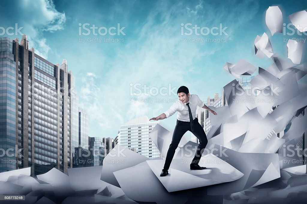 Asian business man surfing on the wave of papers stock photo
