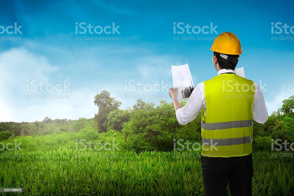 Asian business man wear yellow helmet looking blueprint to build stock photo