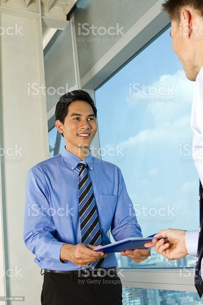 Asian business men submitting a file report royalty-free stock photo