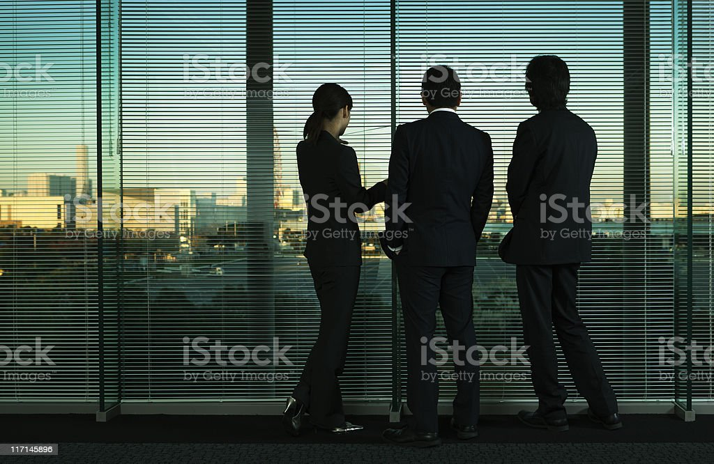 Asian Business Office Workers Silhouetted, Looking at Tokyo City Skyline stock photo
