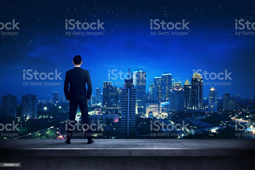 Asian business person standing on the rooftop stock photo
