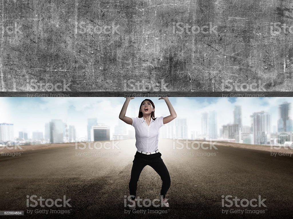 Asian business woman lift heavy block stock photo