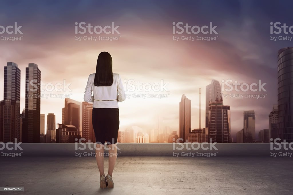 Asian business woman on the roof and looking at the stock photo