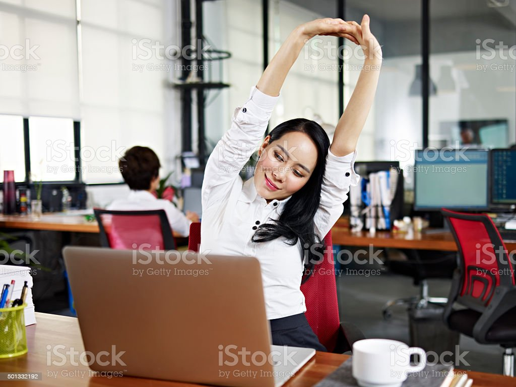 asian business woman stretching arms in office stock photo