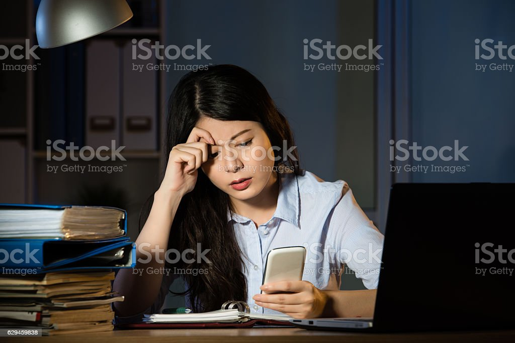 asian business woman text message by smartphone overtime working stock photo