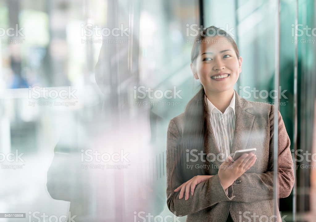 Asian business woman using a smart phone stock photo